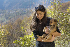 Beautiful young woman laughing and  hugging dog. Happy girl  hugging dog outdoor Stock Photo