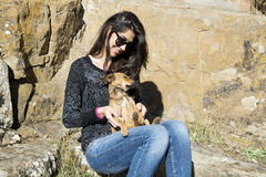 Beautiful young woman laughing and  hugging dog. Happy girl  hugging dog outdoor Royalty Free Stock Image