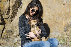 Beautiful young woman laughing and  hugging dog. Happy girl  hugging dog outdoor Royalty Free Stock Images