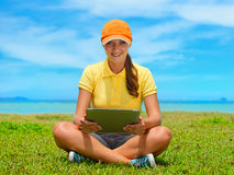 Beautiful young woman on the lawn with her tablet computer Royalty Free Stock Photography