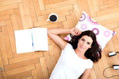 A beautiful young woman laying on the floor, with electronic gad Stock Photography