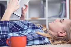 Beautiful young woman laying on the floor at home, reading a book, living room interior. Girl reading a book on the Stock Photo