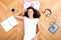 A beautiful young woman laying on the floor, with electronic gad Royalty Free Stock Image