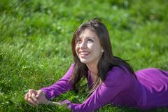 Beautiful young woman laying on grass Stock Images