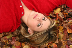 Beautiful Young Woman Laying in Leaves Royalty Free Stock Images