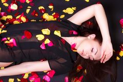 Beautiful young woman laying on sparse rose petals Stock Image