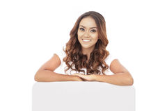 Beautiful young woman lean on white board. Portrait of beautiful young woman lean on white board isolated on white background Royalty Free Stock Images
