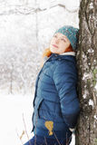 Beautiful young woman leaned to the tree in winter park Royalty Free Stock Photo
