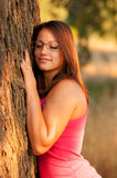 Beautiful young woman leaning against tree Royalty Free Stock Photo