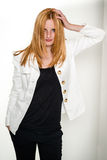 Beautiful young woman leaning against wall. Portrait of beautiful young blond woman in white jacket and black shirt leaning against wall, isolated on white Stock Photos