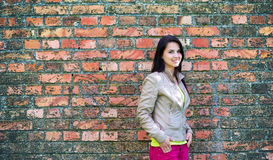 Beautiful young woman leaning against a wall Royalty Free Stock Images