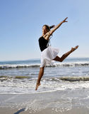 Beautiful young woman leaping on beach Royalty Free Stock Image