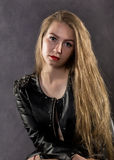 Beautiful young woman in a leather jacket posing on a gray background royalty free stock image