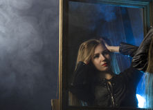 Beautiful young woman in a leather jacket posing on a mirror background stock image
