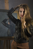 Beautiful young woman in a leather jacket posing on a mirror background stock photos