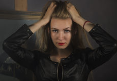 Beautiful young woman in a leather jacket posing on a mirror background royalty free stock photo
