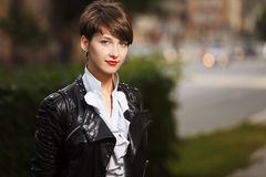 Happy young fashion business woman in leather jacket walking in city street royalty free stock photography