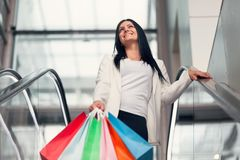 Beautiful woman leaving the mall with plenty of shopping bags stock image
