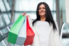 Beautiful woman leaving the mall with plenty of shopping bags. Beautiful young woman leaving the mall with plenty of shopping bags Royalty Free Stock Photos
