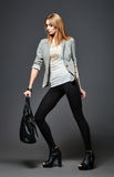 Beautiful young woman in leggings, jacket and shirt, with bag in hand Royalty Free Stock Image