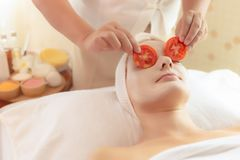 Beautiful young woman lie down on spa bed in spa room at spa salon. Masseuse put tomato slices on customer eyes for making bright stock image
