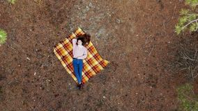 AERIAL: A beautiful young woman lies on a carpet in the middle of the pine forest The camera is smoothly moving away