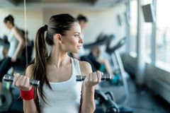 Beautiful, young woman lifting weights in a gym Royalty Free Stock Photography