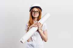 Beautiful young woman on a light background holds blueprints, design, engineer Royalty Free Stock Image