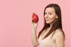 Beautiful young woman in light clothes holding fresh ripe pitahaya, dragon fruit isolated on pink pastel wall background. In studio. People vivid lifestyle royalty free stock photos