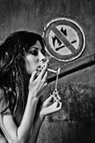 Beautiful young woman lights cigarette near Stock Photos