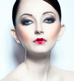 Beautiful young woman like doll with a glamorous cool makeup Stock Photo