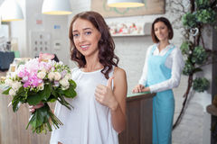 Beautiful young woman likes flowers in store Royalty Free Stock Photography