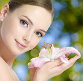 Beautiful young woman with lily flower in hands Royalty Free Stock Photography