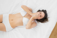 Beautiful young woman in lingerie yawning on bed Royalty Free Stock Photo