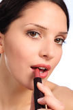 Beautiful young woman lipstick cosmetics to lips Stock Photos