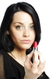 Beautiful young woman with lipstick in her hand Royalty Free Stock Photos