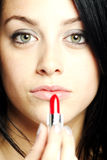 Beautiful young woman with lipstick in her hand Stock Photography
