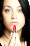 Beautiful young woman with lipstick in her hand Royalty Free Stock Photography