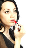 Beautiful young woman with lipstick in her hand Stock Images
