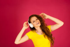 Beautiful young woman listen to the music over vibrant color bac Stock Photos