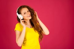 Beautiful young woman listen to the music over vibrant color bac Stock Photography