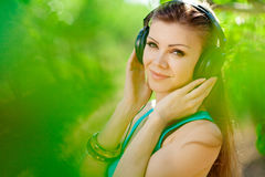 Beautiful young woman listen to music wearing headphones outdoor Stock Photography