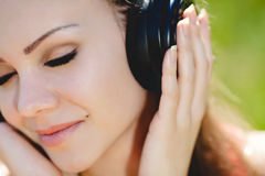 Beautiful young woman listen to music wearing headphones outdoors Stock Photography