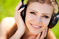 Beautiful young woman listen to music wearing headphones outdoors Royalty Free Stock Image