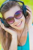 Beautiful young woman listen to music wearing headphones outdoors Royalty Free Stock Images