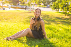 Beautiful young woman listening music in the park Royalty Free Stock Photography