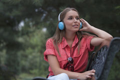 Beautiful young woman listening musing through headphones in park stock photography
