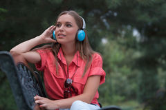 Beautiful young woman listening musing through headphones in park Stock Images