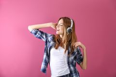 Beautiful young woman listening to music. In headphones on color background Stock Photos