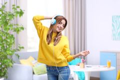 Beautiful young woman listening to music. In headphones at home Stock Photos